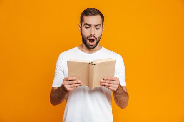 Imagem de um homem intrigado de 30 anos em uma camiseta branca segurando e lendo um livro, isolado