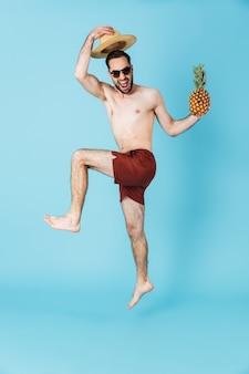 Imagem de um homem jovem e bonito verão feliz pulando isolado sobre uma parede azul segurando abacaxi.