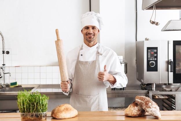 Imagem de um homem sorridente, padeiro de uniforme branco, em pé na padaria com pão na mesa