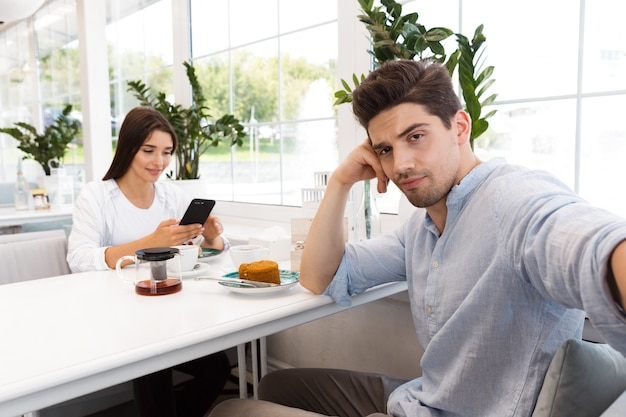 Imagem de um homem triste e descontente tirar selfie enquanto sua namorada conversando por telefone, sentado no café.