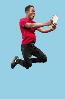Imagem de um jovem africano feliz e animado pulando isolado sobre um fundo amarelo usando um laptop
