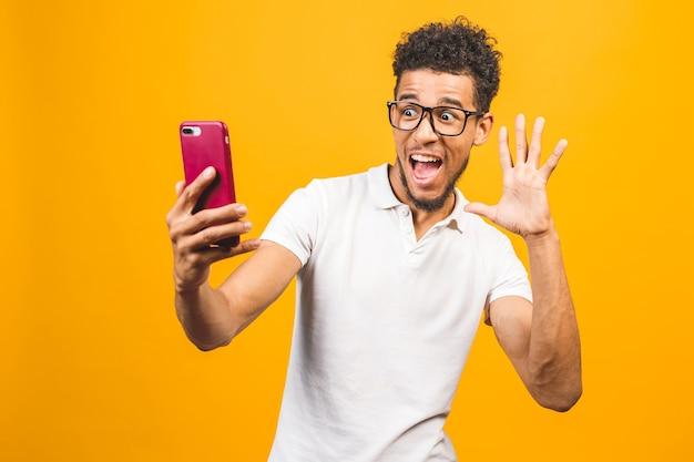 Imagem de um jovem afro-americano feliz posando isolado sobre um fundo amarelo