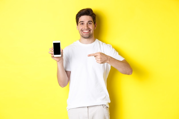 Imagem de um jovem atraente apontando o dedo para a tela do smartphone, mostrando um aplicativo, em pé contra um fundo amarelo