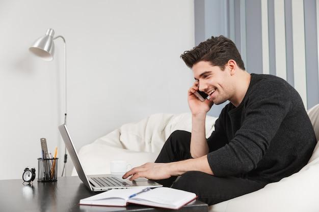 Imagem de um jovem bonito feliz em casa dentro de casa usando o computador laptop, falando pelo telefone celular.