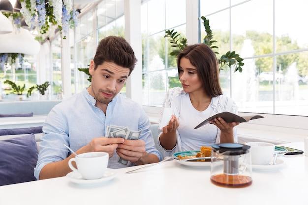 Imagem de um jovem casal amoroso confuso descontente, sentado no café, segurando cheque e dinheiro.