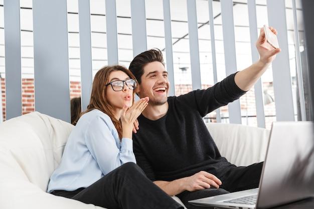 Imagem de um jovem casal amoroso feliz em casa dentro de casa usando o computador laptop faz um selfie por telefone.