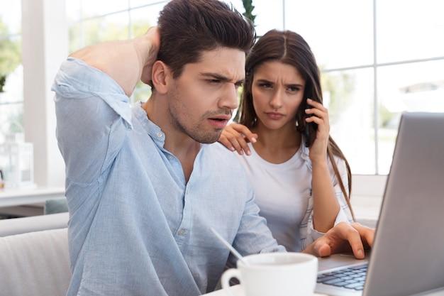 Imagem de um jovem casal apaixonado descontente confuso, sentado no café, usando o computador portátil, falando por telefone.
