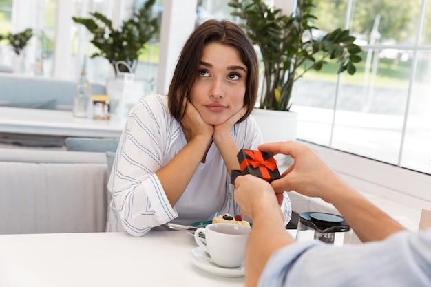 Imagem de um jovem casal apaixonado, sentado no café. homem dá um presente para sua namorada triste.