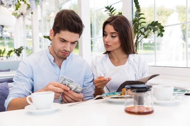 Imagem de um jovem casal apaixonado, sentado no café, segurando cheque e dinheiro.