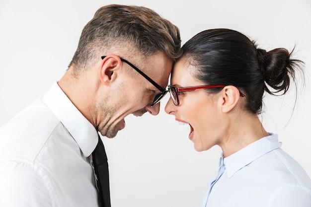 Imagem de um jovem casal de colegas de trabalho com raiva isolado sobre uma parede branca, falando um com o outro.