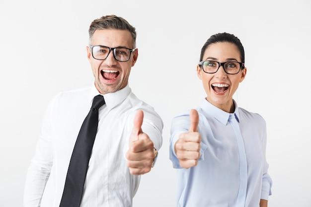 Imagem de um jovem casal de colegas de trabalho feliz isolado sobre a parede branca, mostrando os polegares.