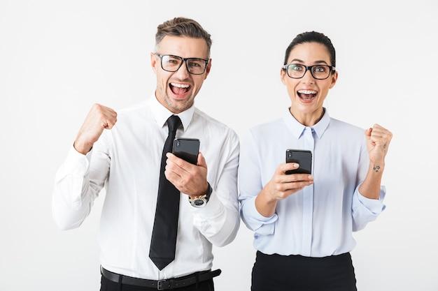 Imagem de um jovem casal de colegas de trabalho feliz isolado sobre uma parede branca usando telefones celulares faz o gesto de vencedor.