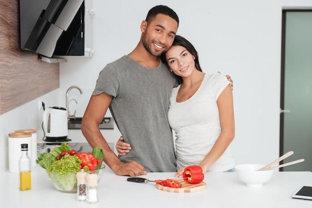 Imagem de um jovem casal feliz na cozinha se abraçando enquanto cozinha. olhando para a frente.