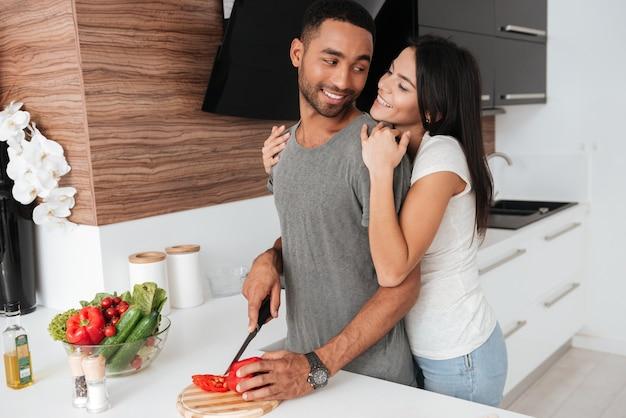 Imagem de um jovem casal feliz na cozinha se abraçando enquanto cozinha.