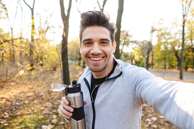 Imagem de um jovem desportista bonito ao ar livre no parque ouvindo música com fones de ouvido tirar uma selfie pela câmera.