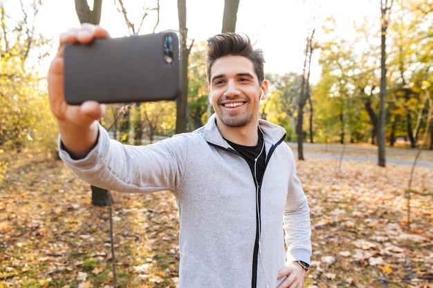 Imagem de um jovem desportista bonito ao ar livre no parque, ouvindo música com fones de ouvido, tire uma selfie pelo telefone celular.