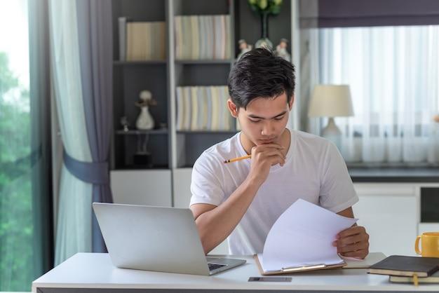 Imagem de um jovem empresário asiático analisando o trabalho usando um laptop em casa.
