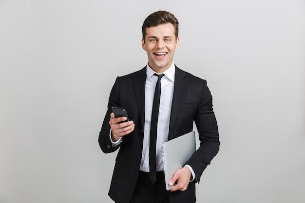 Imagem de um jovem empresário feliz em um terno formal sorrindo enquanto segura o laptop e o celular isolados