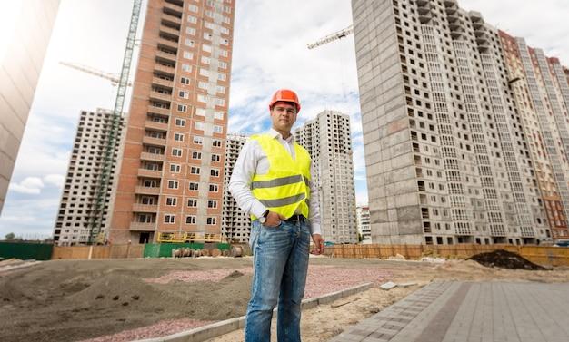 Imagem de um jovem engenheiro com capacete e colete de segurança posando contra edifícios em construção