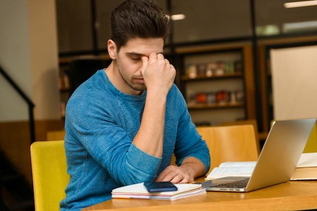 Imagem de um jovem estudante concentrado homem com dor de cabeça na biblioteca, fazendo lição de casa, estudando ler e usando o computador portátil.