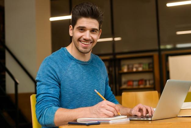 Imagem de um jovem estudante feliz na biblioteca fazendo lição de casa, estudar ler e usar o computador portátil.