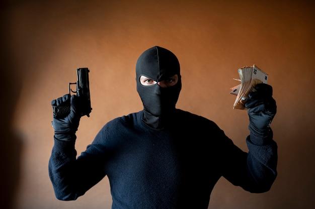 Imagem de um ladrão na balaclava com uma arma na mão e muito dinheiro na outra mão