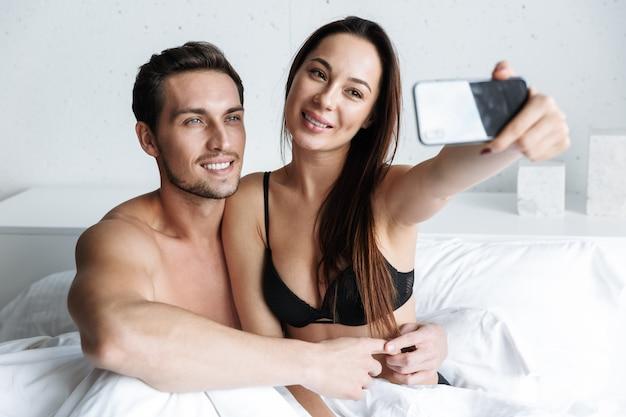 Imagem de um lindo casal, um homem e uma mulher, tirando uma foto de selfie juntos, enquanto está deitado na cama em casa ou em um apartamento de hotel