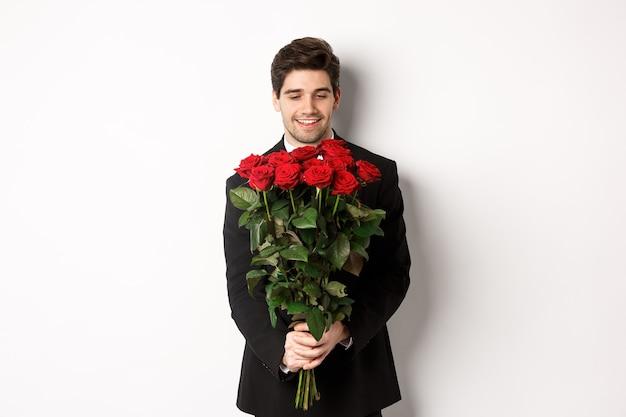 Imagem de um lindo namorado em um terno preto, segurando um buquê de rosas vermelhas e sorrindo, estando em um encontro, em pé sobre um fundo branco