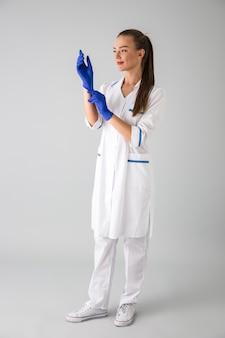 Imagem de um médico cosmetologista bela jovem isolada sobre uma parede cinza.