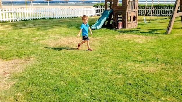 Imagem de um menino feliz sorrindo e rindo correndo na grama verde no parquinho infantil