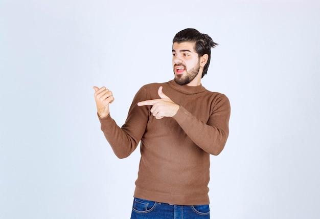 Imagem de um modelo de jovem bonito em pé e apontando para cima com os dedos. foto de alta qualidade