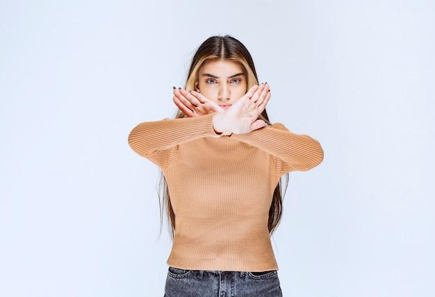 Imagem de um modelo de jovem com suéter marrom em pé e fazendo gesto de parada.