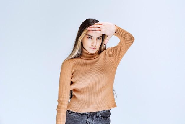 Imagem de um modelo de jovem com suéter marrom em pé e fazendo o sinal de pare.