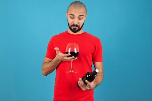 Imagem de um modelo de jovem em t-short vermelho segurando uma garrafa de vinho com um copo.