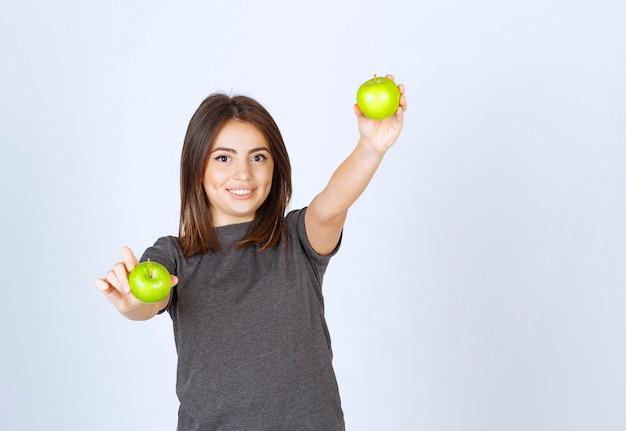 Imagem de um modelo de jovem segurando duas maçãs verdes.