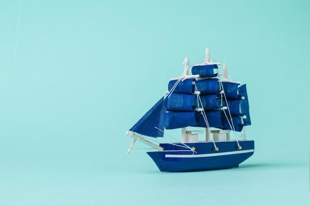 Imagem de um modelo de veleiro em uma superfície azul clara. o conceito de viagem e aventura.