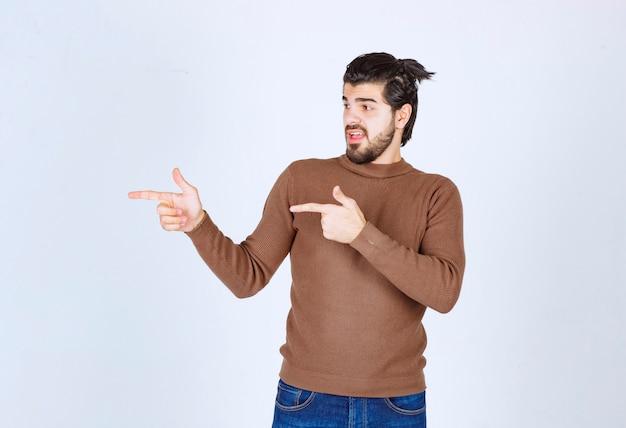 Imagem de um modelo jovem bonito em pé e apontando com os dedos. foto de alta qualidade