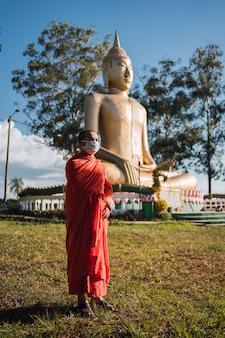 Imagem de um monge budista com máscara protetora ao lado do buda gigante na américa do sul.