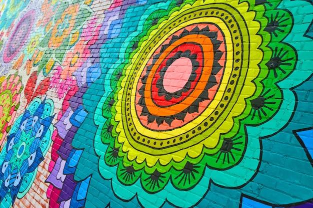 Imagem de um mural de flores em arco-íris em uma parede de tijolos