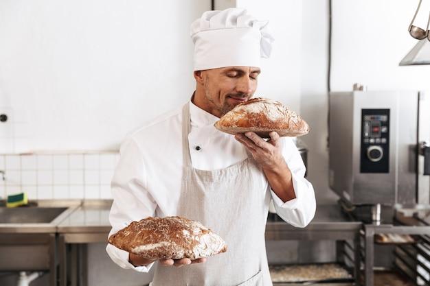 Imagem de um padeiro bonito de uniforme branco em pé na padaria e segurando um pão