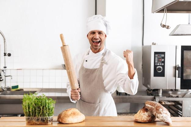 Imagem de um padeiro de 30 anos em uniforme branco sorrindo, em pé na padaria com pão na mesa