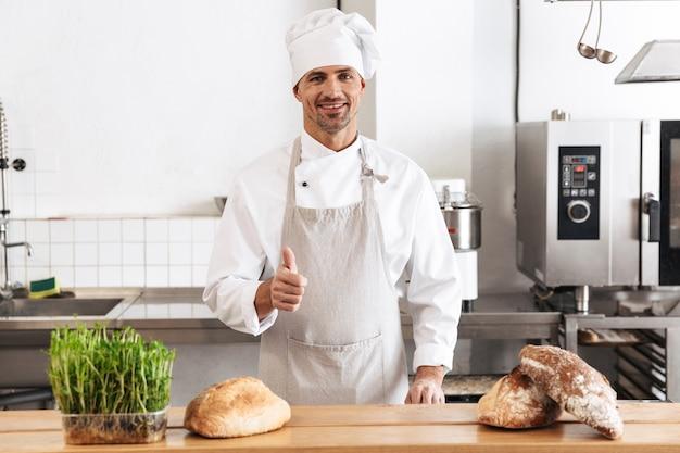 Imagem de um padeiro europeu em uniforme branco sorrindo, em pé na padaria com pão na mesa