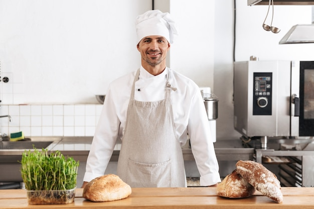 Imagem de um padeiro homem caucasiano em uniforme branco sorrindo, em pé na padaria com pão na mesa