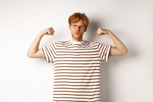 Imagem de um ruivo forte e confiante flexionando os bíceps, mostrando os músculos depois da academia, em pé sobre um fundo branco