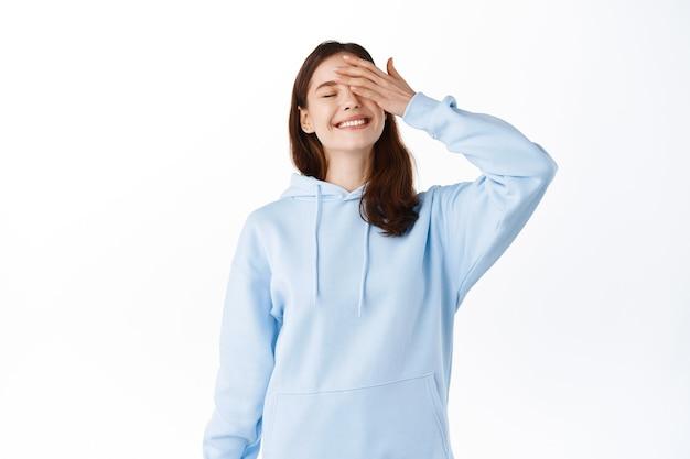 Imagem de uma adolescente feliz e despreocupada sorrindo e tocando o rosto com a mão, olhos fechados com alegria, sentindo-se relaxada e otimista, em pé contra uma parede branca