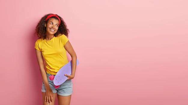 Imagem de uma adorável adolescente feliz com cabelo encaracolado posando em uma camiseta amarela