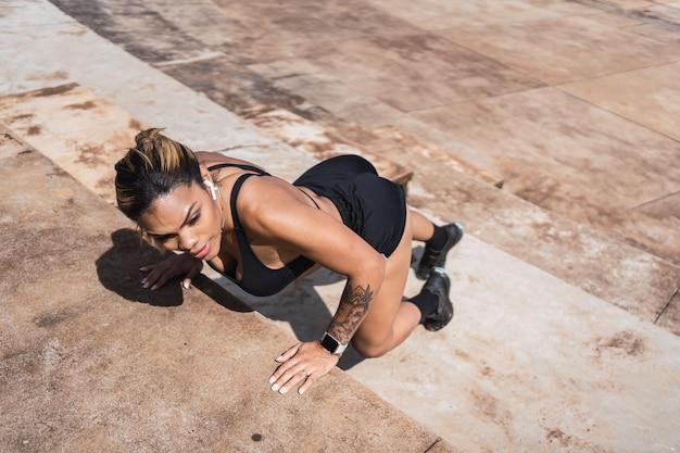 Imagem de uma atleta latino-americana se exercitando em um parque urbano.