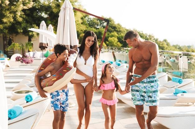 Imagem de uma atraente família caucasiana com filhos caminhando perto de uma piscina luxuosa e carregando um anel de borracha na frente do hotel