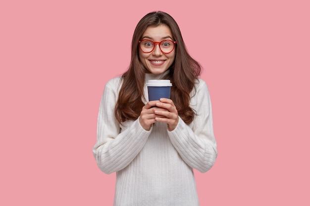 Imagem de uma atraente senhora de cabelos escuros segurando um café ou chá para viagem e aproveitando o tempo livre