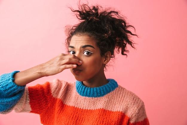 Imagem de uma bela jovem africana posando nariz de cobertura isolado.